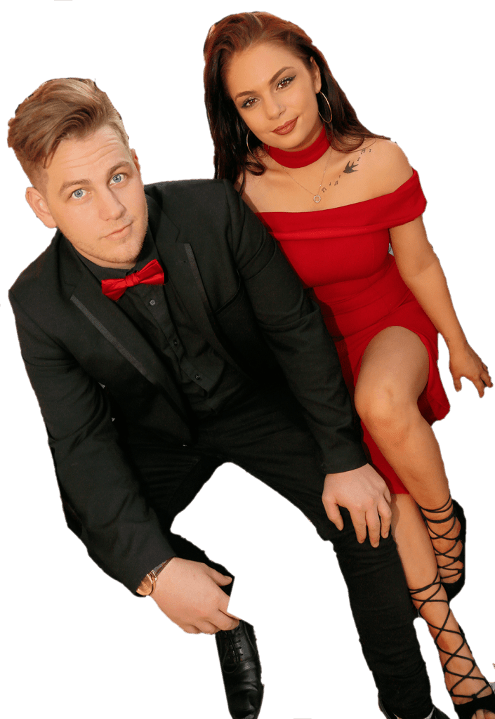 a male musician in a black suit with a red bowtie and a female musician in a red dress with long hair